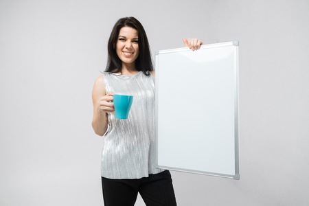 Charming young brunette girl holding Cup and empty magnetic Board isolated on white wall background. Business woman portrait with cup. Delicious coffee. a place for a label Фото со стока