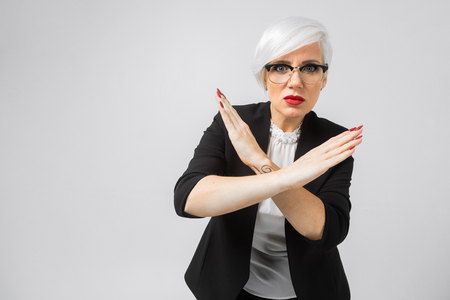 Portrait of serious, unhappy, confident woman holding two arms crossed, gesturing no sign. I said, no! Angry and frustrated woman shows her crossed arms in x gesture sign and looks on camera. Stop sign