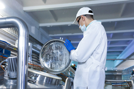 Technologist in a cap, mask and white coat is in the production shop. inspector removes the indicators at the dairy plant. Engineer keeps statistics on production