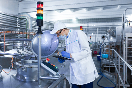 technologist in the cap, mask and white coat stands in the production shop and makes notes with a pen in the sheet. The inspector removes the indicators at the dairy plant. Engineer keeps statistics on production