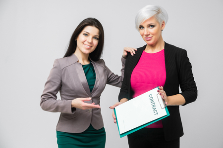 Two business women present the contract in isolation in a light Studio. business and entrepreneurship concept. lovely women offer to sign a contract