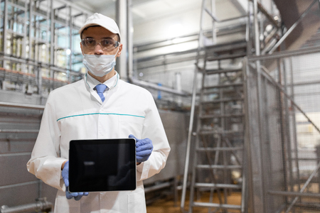 Place for writing. The technologist in a mask, gloves and a white robe stands with a tablet with an empty screen at the factory. A man with a digital tablet in uniform in the production shop