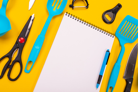 Modern kitchen tools and a clean white sheet between them isolated on a yellow tablecloth. Kitchen accessories design concept. Place for writing. Set of kitchen knives. Detailed kitchen utilities