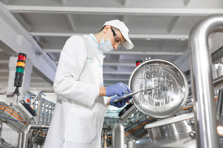 Technologist in a cap, mask and white coat is in the production shop and holding a digital tablet. inspector removes the indicators at the dairy plant. Engineer keeps statistics on production Stok Fotoğraf