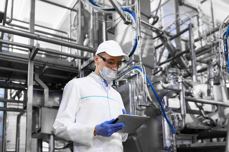 concentrated technologist taking necessary notes with help of digital tablet while standing at production department of dairy factory. inspector carries out control at the cheese factory Foto de archivo
