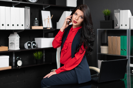lawyer works at laptop computer in stylish office. bright Young girl sat down on table with phone in her hand in her office. Businesswoman working in stylish office Imagens