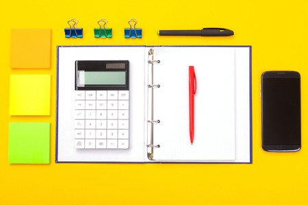 Office desk flat lay. Top view of working space table with calculator, notebook and stationery, office supplies on colored yellow background. Back to school concept