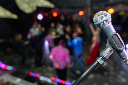 Close up of microphone in concert hall or conference room. Microphone on stage against a background of auditorium. Public performance on stage Microphone on stage against a background of auditorium. Shallow depth of field. Public performance on stage