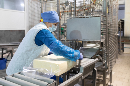 An employee in a blue form packs a large piece of oil into a transparent film on the production line . The production process at the dairy plant Stock Photo