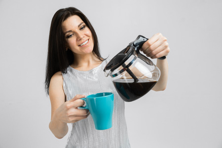 Girl pours coffee from the coffee pot. barista girl with coffee Moka pot and cup isolated on white background. Pretty woman pouring hot water from the kettle into a cup Reklamní fotografie