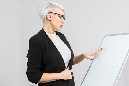 young woman holding white board. Pretty business woman holding a white blank board over white background. Businesswoman presenting sign against