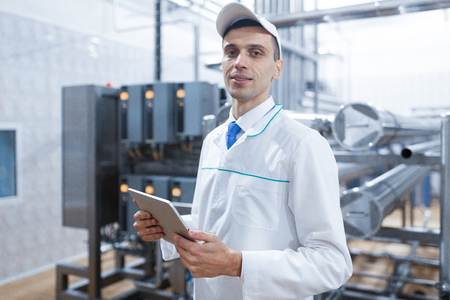 Technologist in a white coat makes the necessary entries in the tablet is at the factory. A man with a digital tablet in uniform in the production shop. interior of production department on background Foto de archivo - 117074426