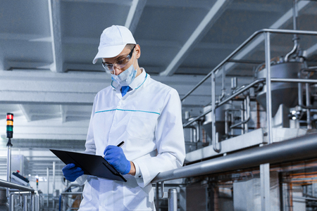 technologist in the cap, mask and white coat stands in the production shop and makes notes with a pen in the sheet. The inspector removes the indicators at the dairy plant. Engineer keeps statistics o