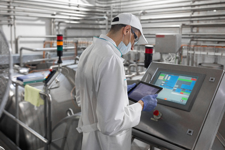 Technologist in a white coat, gloves and a mask holding a tablet and is near the information unit with the monitor in the factory of dairy products. The inspector checks the performance at the production plant Imagens