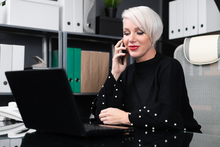 stylish woman with white short hair works at laptop with phone in dark office. Adult woman at computer. portrait of businesswoman in office at computer Desk