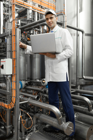 technologist in a white coat makes the necessary entries in the laptop at the factory. Working with a laptop in the production shop. Engineer with a laptop computer in his hands understands the device of the pipeline