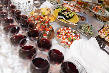 Beautifully decorated catering banquet table with different food snacks and appetizers with sandwich, caviar, fresh fruits on corporate party event or wedding celebration. Lots of traditional festive food on wooden table