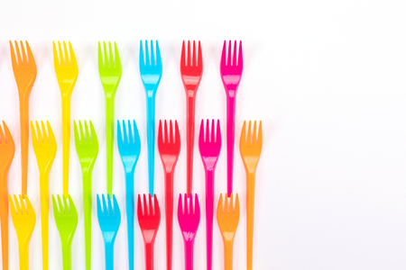Composition of colorful plastic forks on a bright background top view
