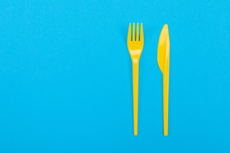 Disposable colorful set of vibrant forks and knifes isolated on blue background. Mock-up Stock Photo