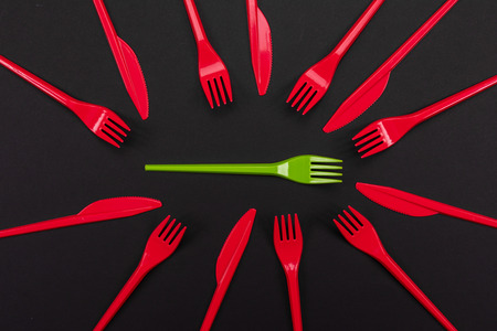 Top view of red and green plastic forks. One green fork surrounded by red forks and knifes Reklamní fotografie