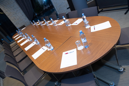 Oval wooden table with sheets of paper, water bottles and glasses next to them waiting for the conference 版權商用圖片