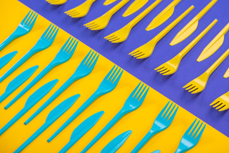 Composition of colorful kitchen cutlery on a bright background top view