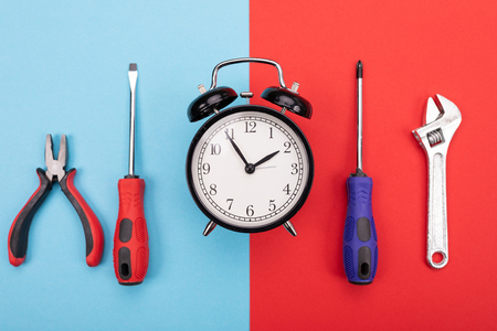 set of tools with alarm clock isolated on blue-red background