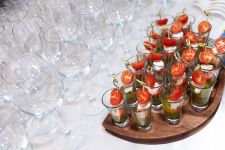 Empty transparent glasses on a long leg and glasses with vegetables on skewers close-up. Buffet table. Festive event. Catering for party. Close up of appetizers with cherry tomatoes Banque d'images