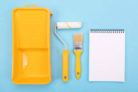 Yelow paint tools. Paint brush and roller with tray for paint and notebook
