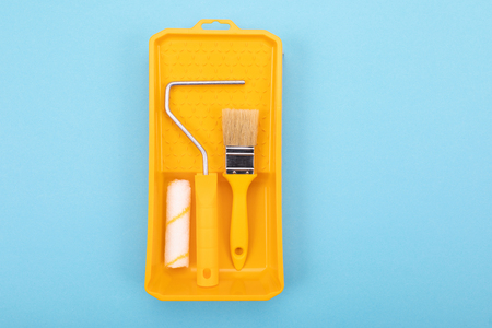 Yelow paint tools. Paint brush and roller with tray for paint