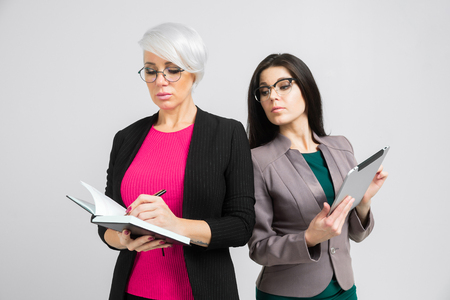 two confident slender buisness ladies holding a notebook and grey tablet. Vertical portrait against wall in studio