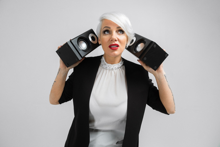 Vertical portrait confident blonde woman with speakers in hands in black costume