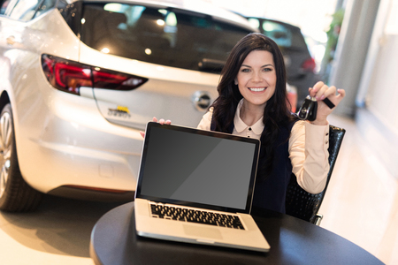 Portrait of beautiful brunet sitting with laptop on chair and holding a keys in car showroom against background of shiny cars, copy space