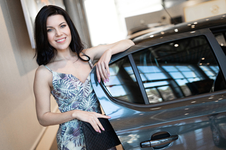 Charming customer brunet possing with a car after buying car in dealeship center