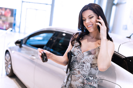Beautiful fashionable brunet handing smartphone and possing near her new car in dealership showroom