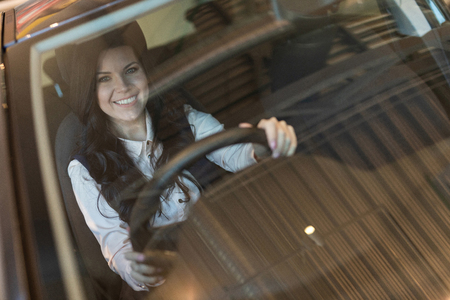 Portrait of smilling happy woman siting in her new vehicle. View through windscreen