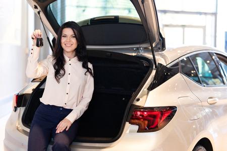 Mujer hermosa en el centro de concesionario quedándose cerca del coche nuevo. Muestra la funcionalidad del coche. Foto de archivo