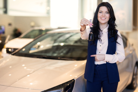 Portrait of smilling happy woman handing a key of her new vehicle