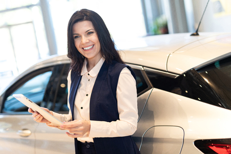 Portrait of beautiful smilling saleswoman handing a tablet present car