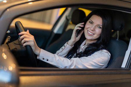 Portrait of smilling happy woman siting in her new vehicle and speaking on smartphone