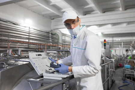 technologist make set up of the special device while standing at the department of dairy factory