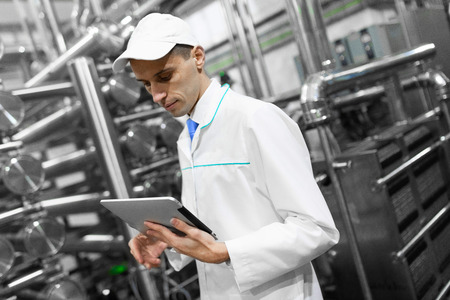 technologist with grey tablet in his hands make a set up of the production line while standing at the department of dairy factory