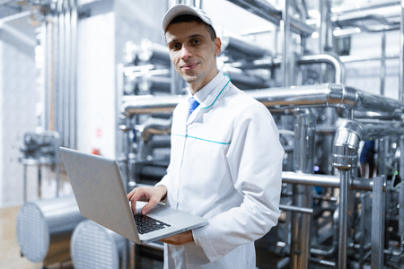 technologist with laptop in his hands make a set up of the production line while standing at the department of dairy factory