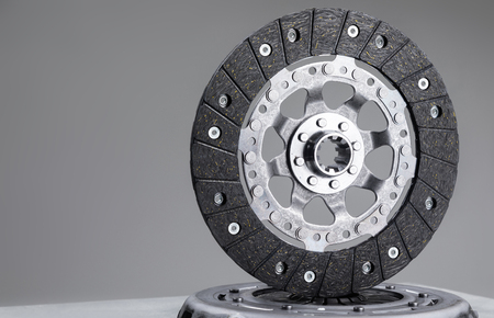 Car clutch plate on a gray background, new part, car warranty service.