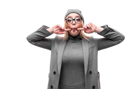 portrait of young smiling joyful blonde girl in coat and hat posing and gesticulating in round glasses on background Stock fotó