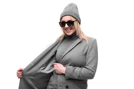 portrait of young smiling joyful blonde girl in coat and hat posing and gesticulating in round glasses on background Banco de Imagens