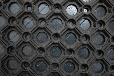 A top view of a black rubber mud mat laying outside the house