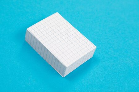 A stack of white scratch paper on azure surface isolated