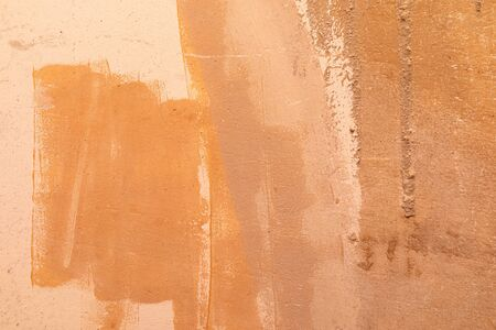 An orange unequally painted concrete wall