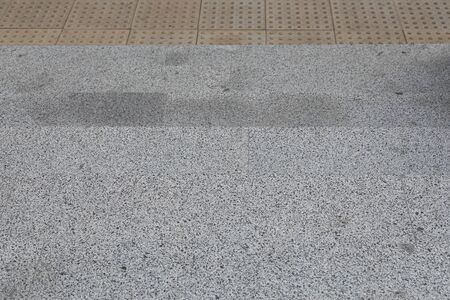 Grey granite tile pavement with line of tactile paving to warn blind people